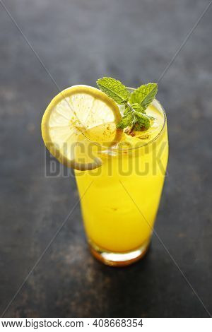 A Close-up Of Glass Of Lemonade With Ice Cubes, Mint Sprig, Lemon Slice And A Pinch Of Turmeric. Yel