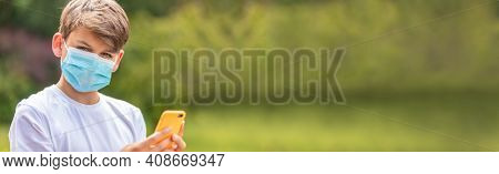 Panorama boy teenager teen male child wearing face mask outside during the Coronavirus COVID-19 virus pandemic using a mobile cell phone for social media or text messaging panoramic web banner header
