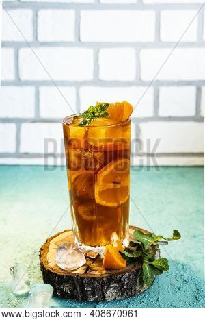 Refreshing Drink, Iced Tea With Ice And Chopped Tangerine In A Glass On A Turquoise Concrete Backgro