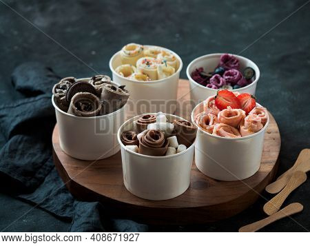 Rolled Ice Cream In Cone Cups On Rustic Round Wooden Tray. Different Thai Style Rolled Ice Cream On