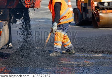 A Road Worker In Orange Overalls Renovates A Section Of The Road With Hot Asphalt Against The Backgr