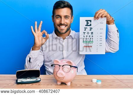 Handsome hispanic man holding optometry glasses and eyesight test doing ok sign with fingers, smiling friendly gesturing excellent symbol