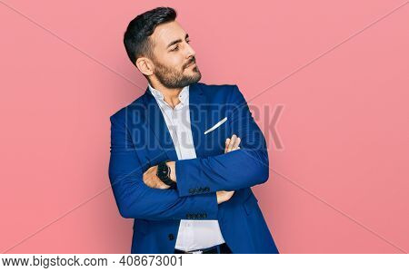 Young hispanic man wearing business jacket looking to the side with arms crossed convinced and confident