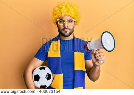 Young hispanic man football supporter holding soccer ball using megaphone relaxed with serious expression on face. simple and natural looking at the camera.