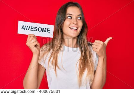 Beautiful caucasian woman holding awesome banner pointing thumb up to the side smiling happy with open mouth