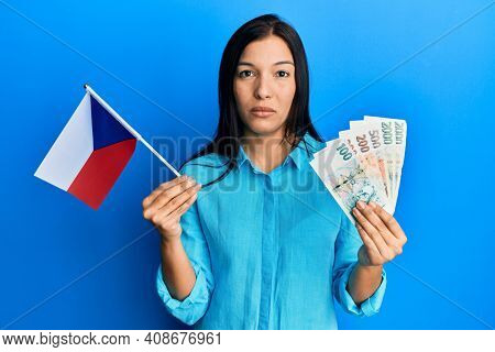 Young latin woman holding czech republic flag and koruna banknotes relaxed with serious expression on face. simple and natural looking at the camera.