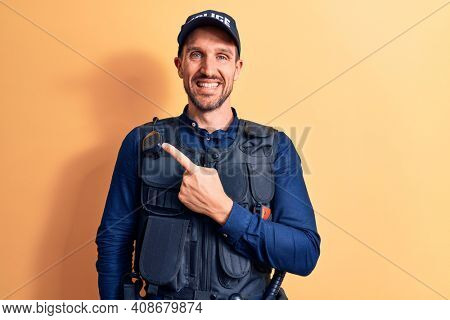 Young handsome policeman wearing police uniform and bulletprof over yellow background smiling cheerful pointing with hand and finger up to the side
