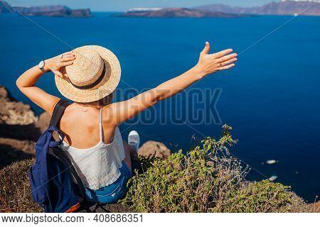 Woman Traveler Sitting On Edge Of Rock Looking At Caldera From Akrotiri, Santorini Island, Greece. H