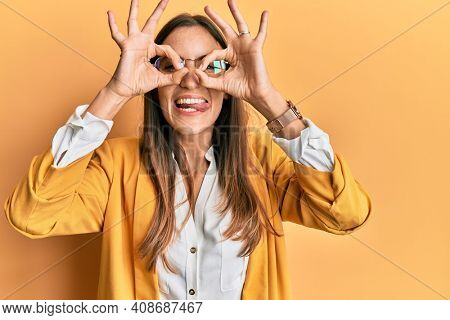 Young beautiful woman wearing business style and glasses doing ok gesture like binoculars sticking tongue out, eyes looking through fingers. crazy expression.