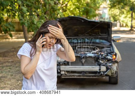 Driver Woman Portrait In Front Of Wrecked Car In Car Accident. Scared Woman In Stress Holding Her He