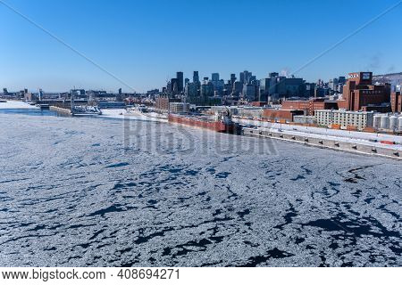 Montreal, Ca - 17 February 2021: View Of Montreal Skyline And Frozen Saint-lawrence River From Jacqu