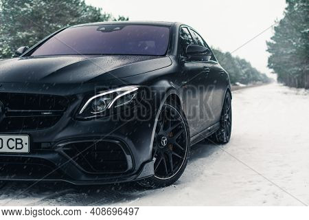 Kherson, Ukraine - February 2021. Powerful Mercedes-amg E63s Brabus 800 In A Black Color On The Empt