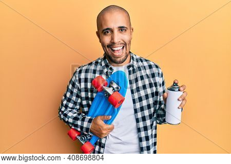 Hispanic adult skater man holding skate and graffiti spray smiling and laughing hard out loud because funny crazy joke.