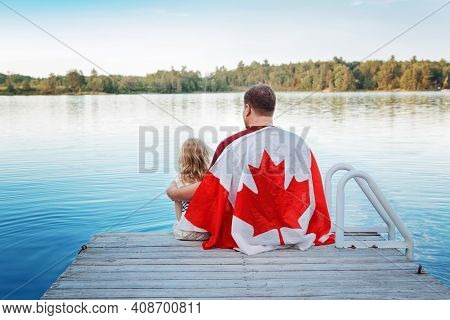 Father And Daughter Wrapped In Large Canadian Flag Sitting On Wooden Pier By Lake. Canada Day Celebr