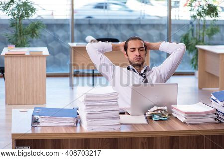 Young male employee unhappy with excessive work in the office