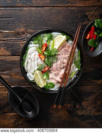Pho Bo Vietnamese Soup With Beef And Noodles On A Wooden Background, View From Above
