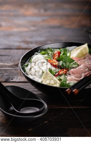 Traditional Vietnamese Soup Pho Bo With Beef And Noodles On A Wooden Background, Selective Focus