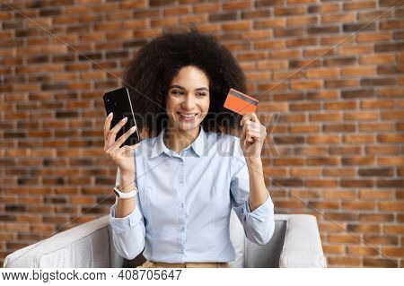 Smiling Mixed-race Ethnic Businesswoman With Curly Hair Holding Mobile Phone, Clarifying Credit Card