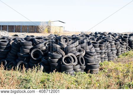 Industrial Landfill For The Processing Of Waste Tires And Rubber Tyres. Pile Of Old Tires And Wheels