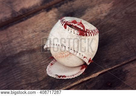 Well loved torn baseball splitting at the seams on a wooden background