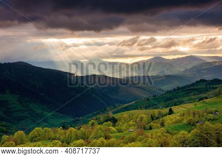 Mountainous Countryside Scenery At Sunset. Dramatic Sky Above The Distant Valley. Green Fields And T