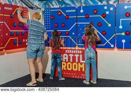 Dnepr, Ukraine- September 06, 2020: Happy Children And Adult Playing On Push Button Game Machine, Fa