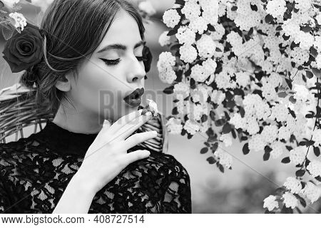 Romantic Girl Or Young Woman With White Flower In Mouth. Spring And Summer. Nature Beauty
