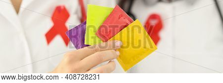 Doctors In White Coats Hold Package Of Condoms In Their Hands. Sexually Transmitted Infection Protec