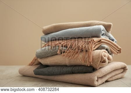 Stack Of Cashmere Clothes On Stone Table