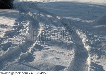 Traces Of Car Tires On The Snow. Sunny Winter Day