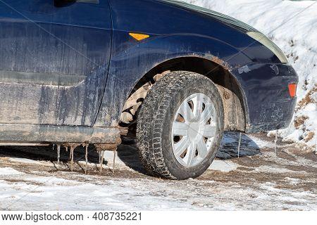 Car With Snow And Salt On A Snowy Road
