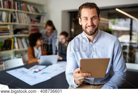Portrait Of Businessman Holding Tablet In Office And Colleagues Discussing In Background