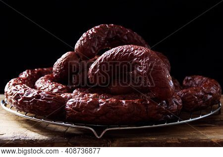 Homemade Venison Sausage On A Rough Wooden Table And On A Dark Background