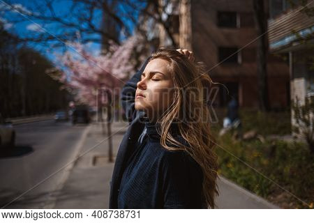 Sakura Branches With Flowers On A Tree On The City Streets. Happy Woman Girl Spinning On The Street