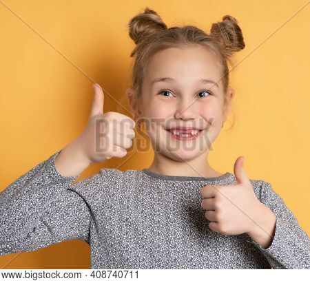 Portrait Of A Cute Baby Girl Smiling Toothlessly And Showing Thumbs Up On A Yellow Background. Close