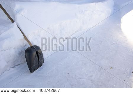 Snow Shovel. Winter Background. A Snow Shovel Stands Next To A Pile Of Snow. To Rake Paths In Winter