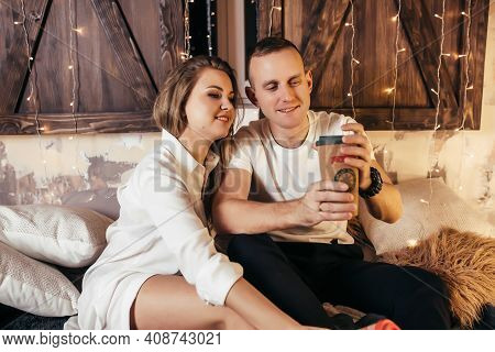The Guy And The Girl Celebrate Christmas And Drink Hot Tea. A Couple In Love Rejoices Each Other On