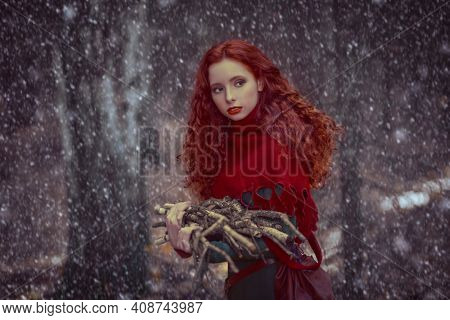 Beautiful redhead girl villager in a historical celtic dress collects brushwood in the forest. Fairytale World. Historical reconstruction.