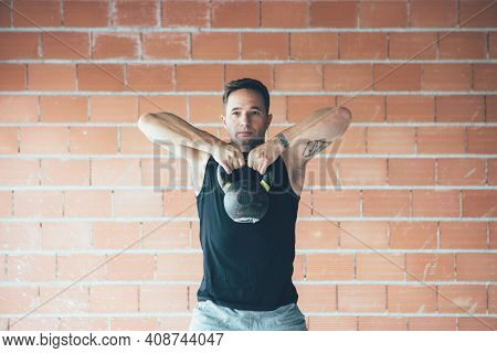 Close Up Of A Fitness Man Doing A Weight Training By Lifting Kettle Bell. Young Athlete Doing Kettle