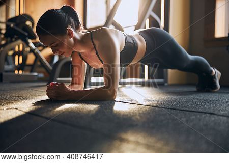 Relaxed Sporty Woman Exercising Core In Gym