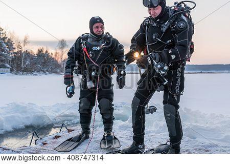 Russia, River Volga Kama - Jan 17th 2020. Diver Checks The Flashlight Torch Before Scuba Ice Diving.