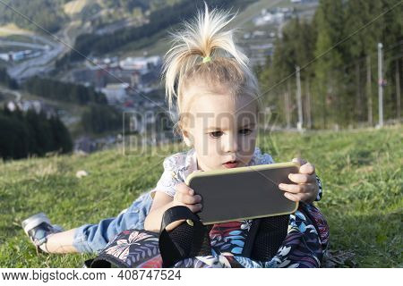 Cute Blond Little Caucasian Child Laying At Green Grass And Looking At Mobile Phone With Interested