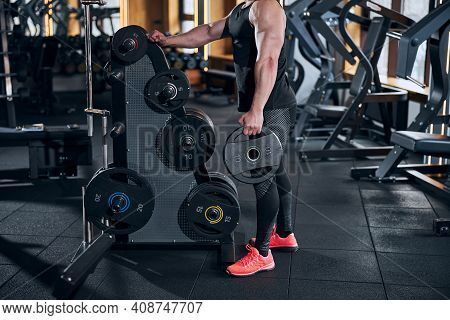 Weightlifter Choosing Equipment For Workout In Gym
