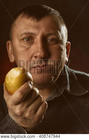 Man Is Eating An Apple. Delicious, Juicy, Common And Healthy Fruit. The Forbidden Fruit.
