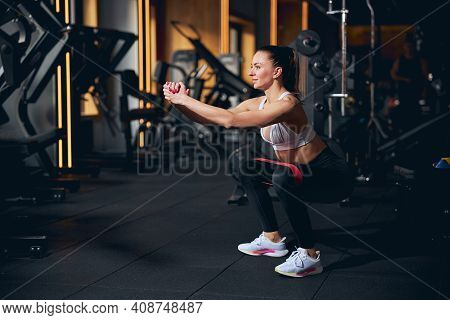 Happy Young Woman Doing Squats In Gym