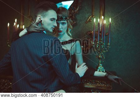 Glamorous passionate man and woman in the style of 1920s in a rich classic interior. Fashion clothes, make-up and hair in luxurious retro style.