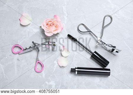 Mascara, Eyelash Curlers And Flower On Light Grey Table, Flat Lay