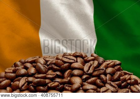 Roasted Coffee Beans On The Background Of The Flag Of The Republic Of Ivory Coast. Concept: Best Fla