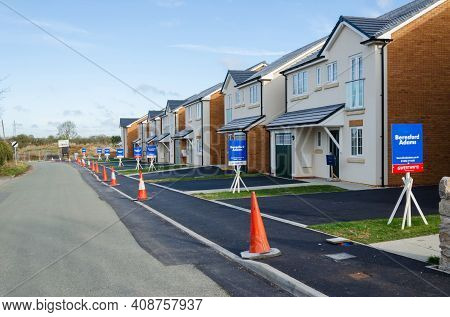 Caerwys, Flintshire; Uk: Feb 11, 2021: New Built Detached Homes Wit A Line Of Estate Agent Sale Boar