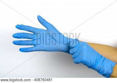 Hands Put On Blue Medical Gloves On A White Background.